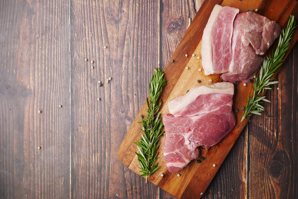 raw meat on brown wooden chopping board