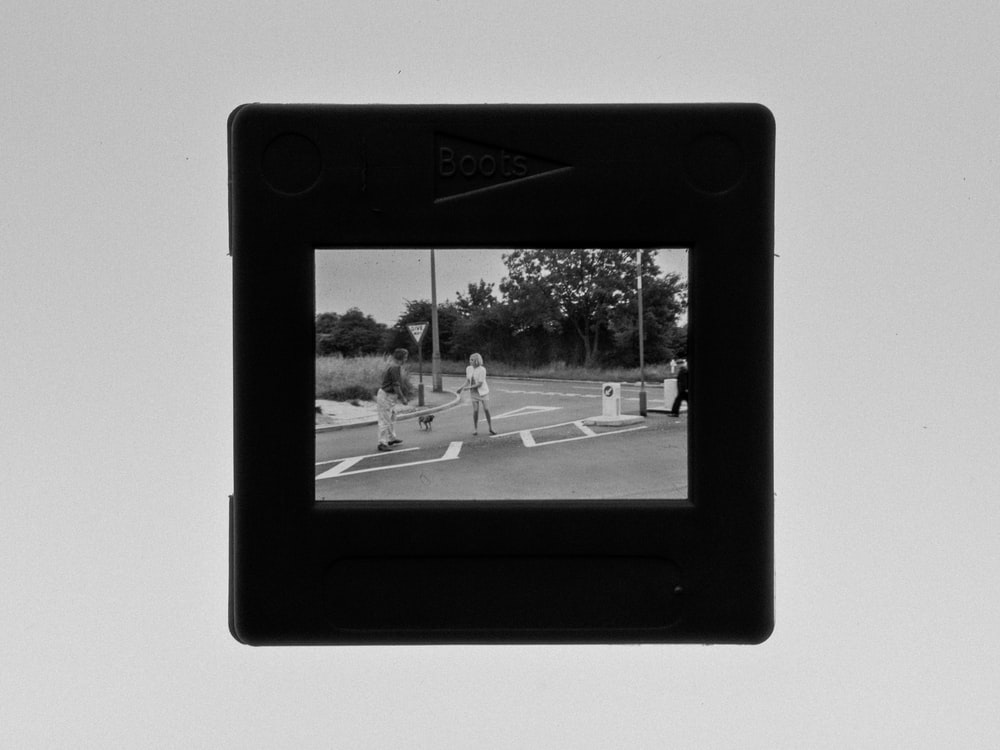 black framed photo of man and woman walking on street