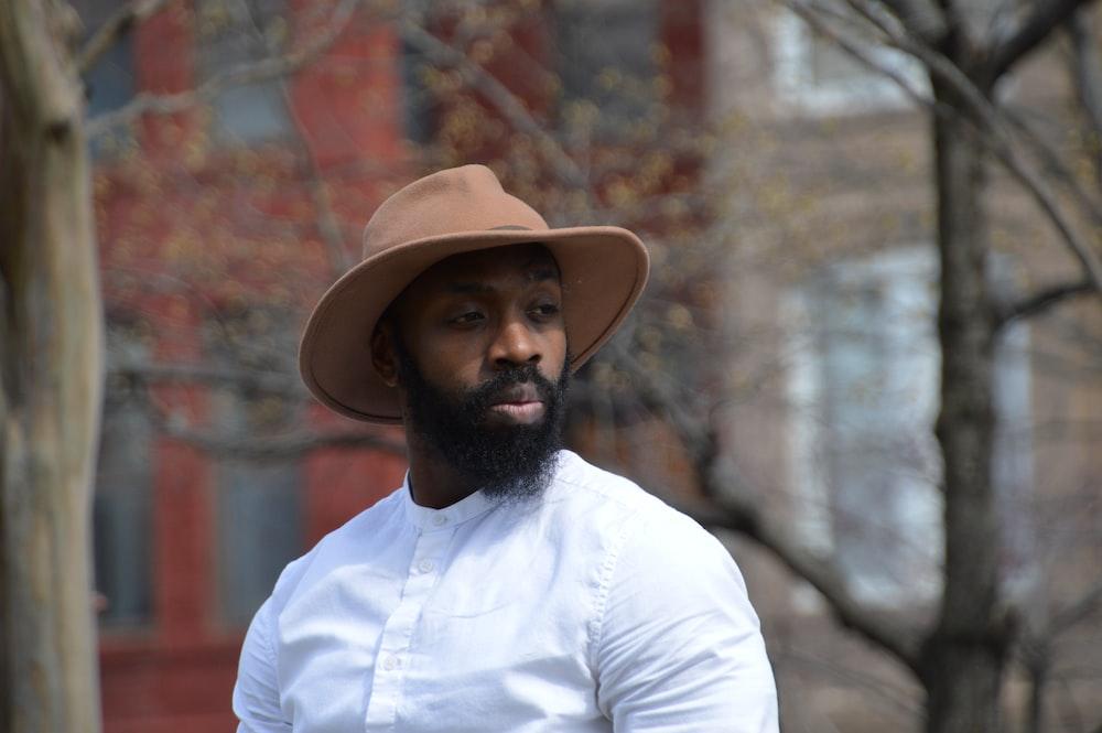 man in white dress shirt wearing brown fedora hat