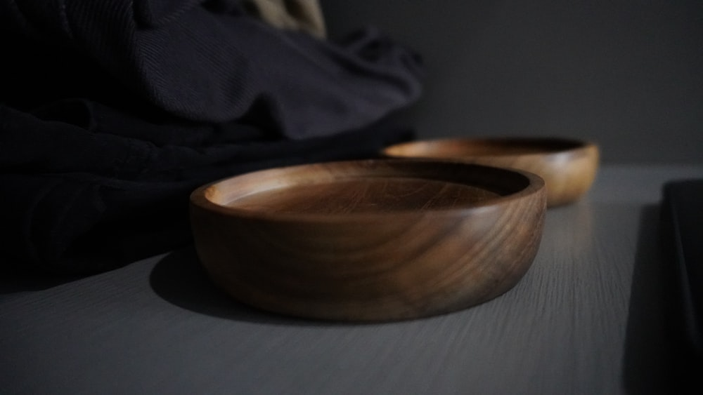 brown round wooden bowl on gray textile