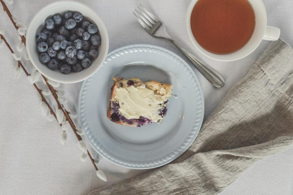 sliced cake on white ceramic plate beside stainless steel fork and knife