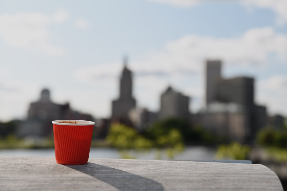 red and white cup on brown wooden table