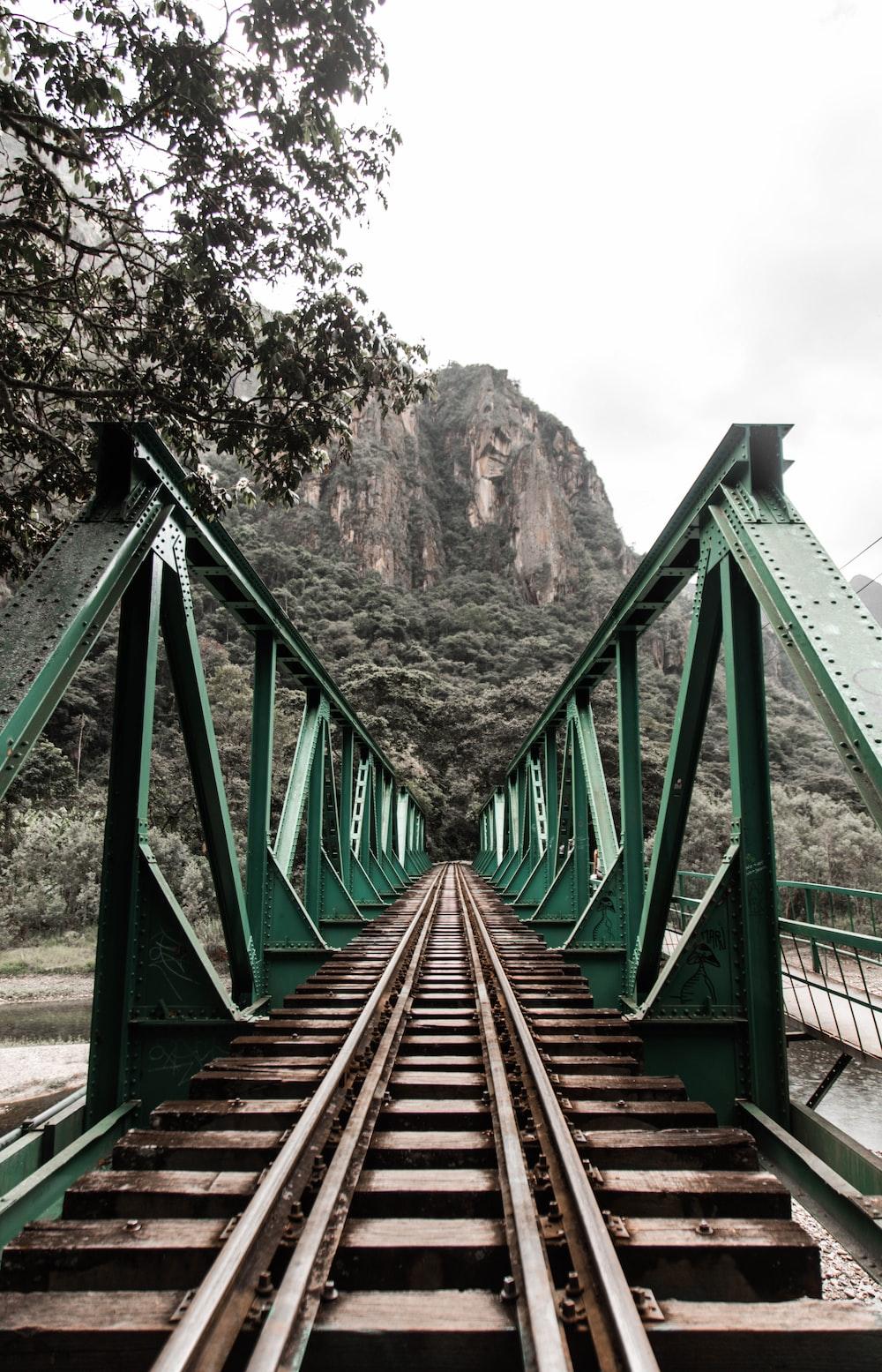 brown wooden bridge near brown mountain during daytime