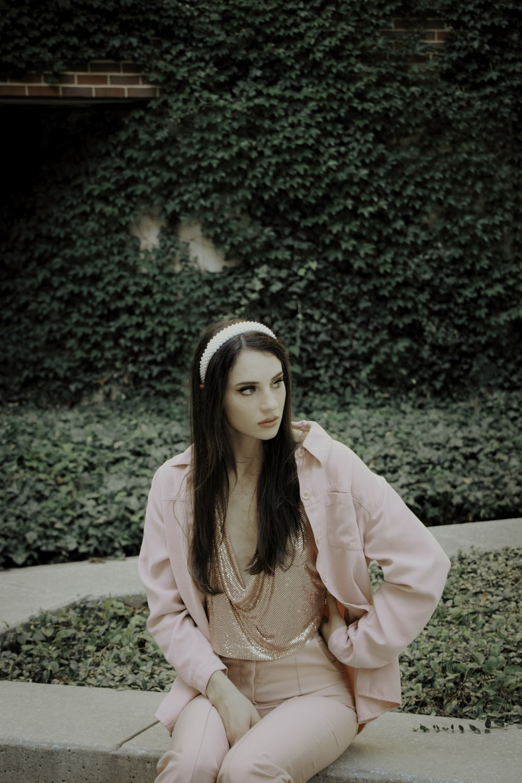 woman in pink blazer standing near green plant