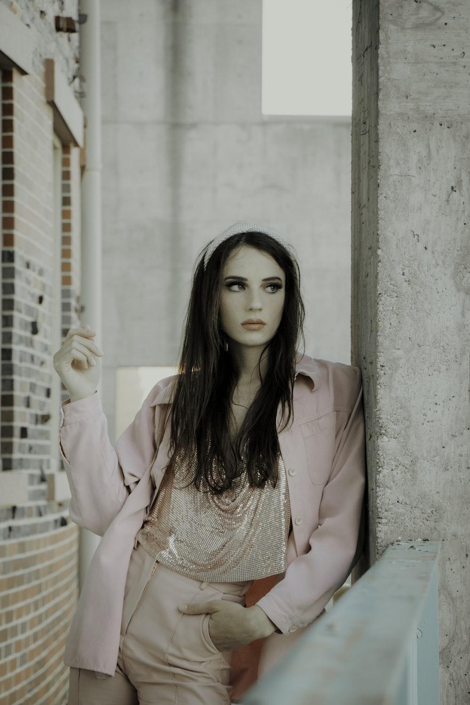 woman in pink blazer sitting on bench
