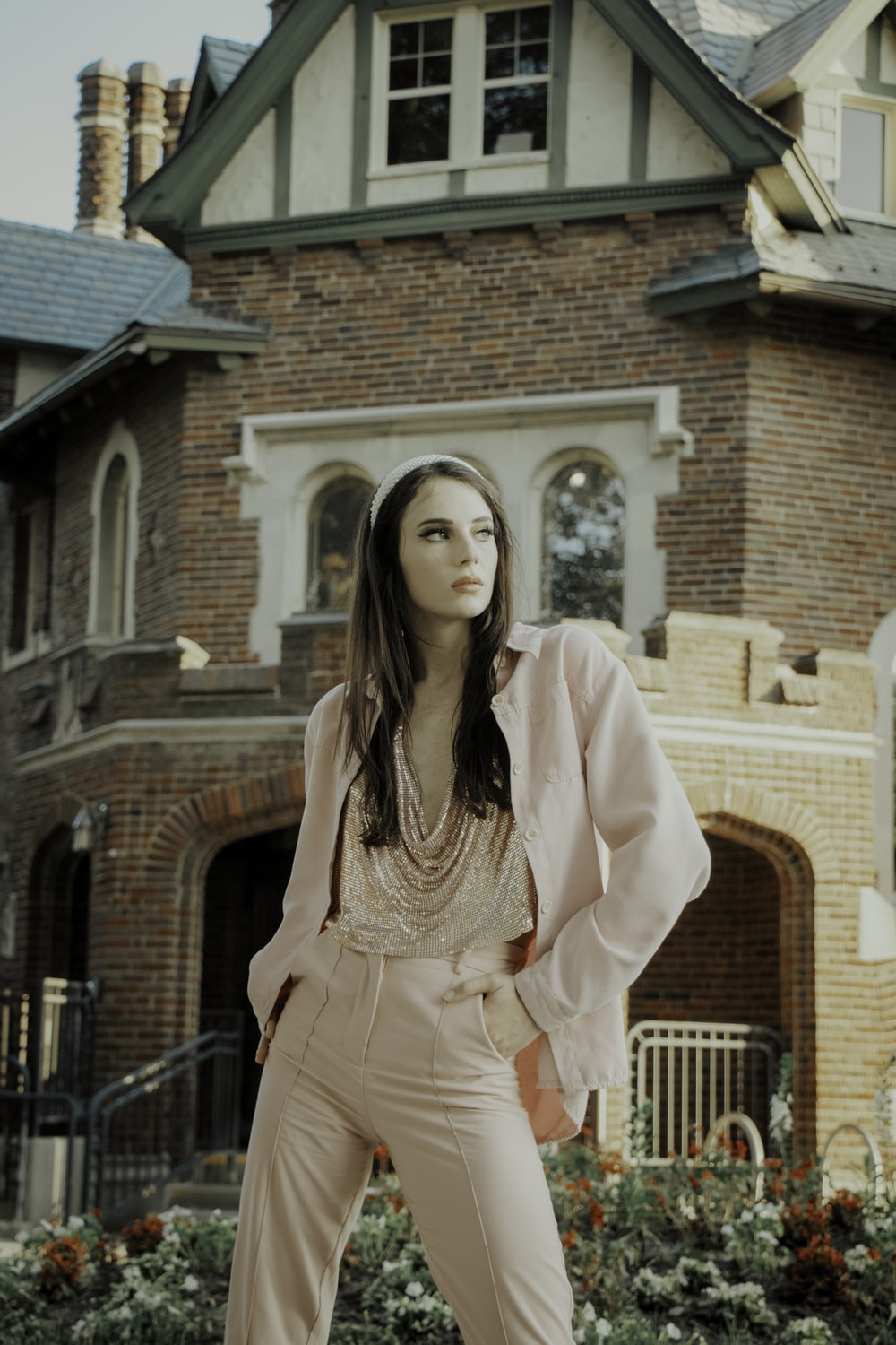 woman in pink long sleeve dress standing near brown brick building during daytime
