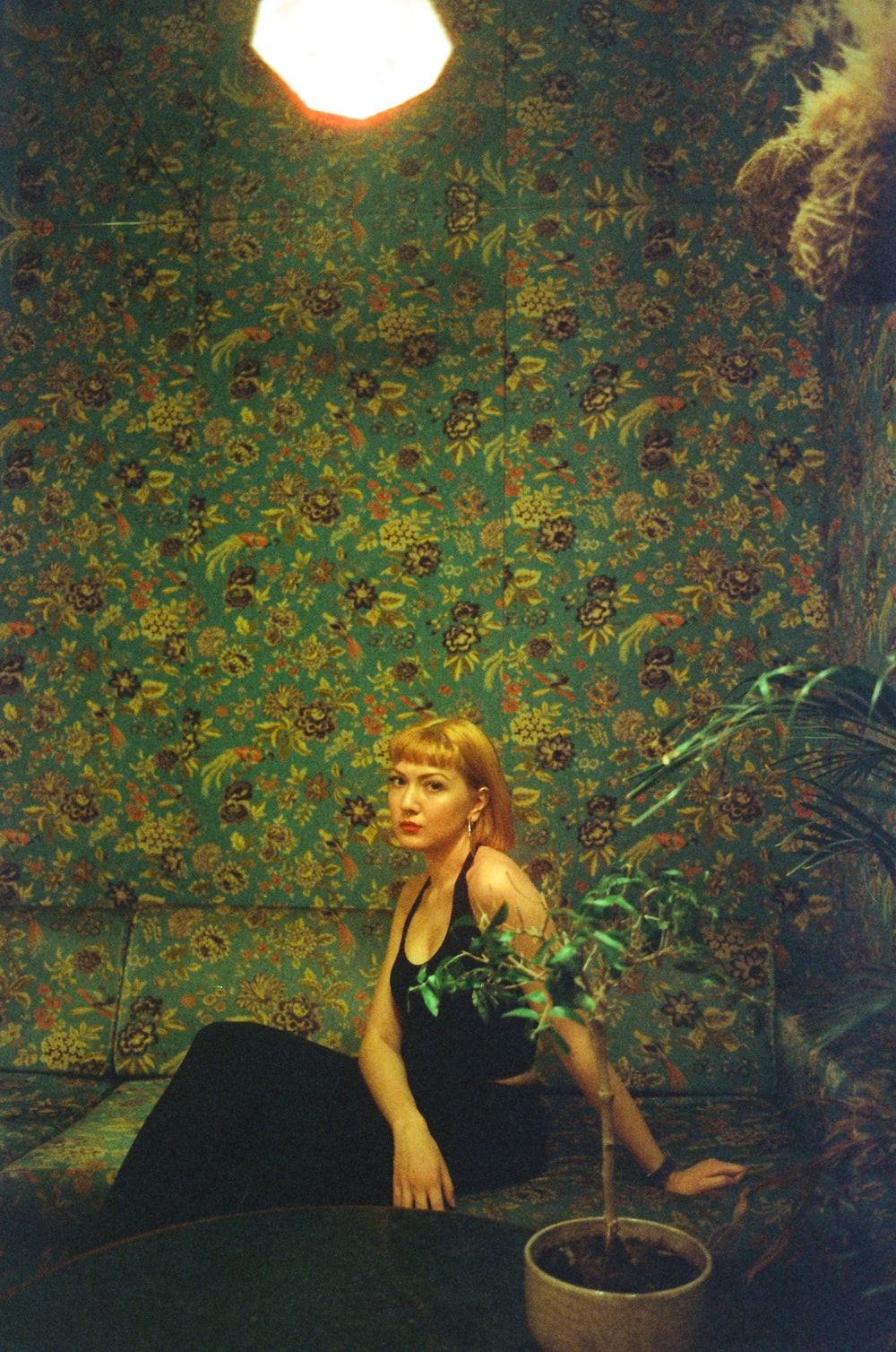 woman in black tank top standing beside green and brown floral wall