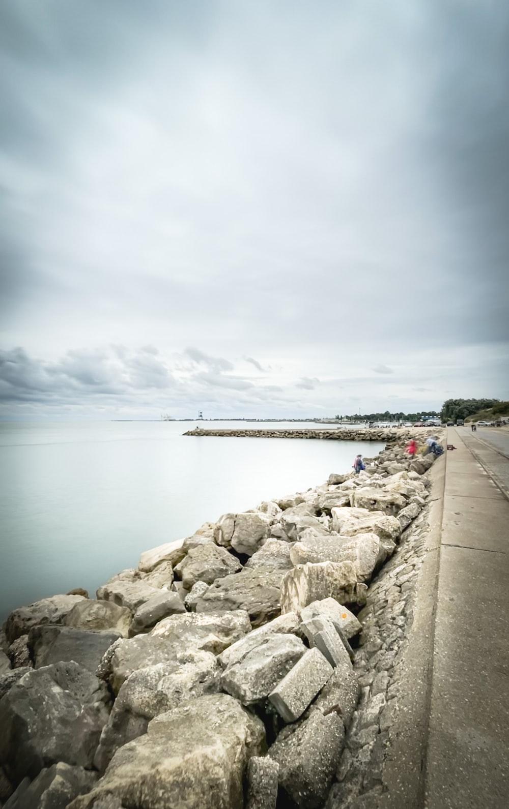 gray rocks near body of water under gray sky