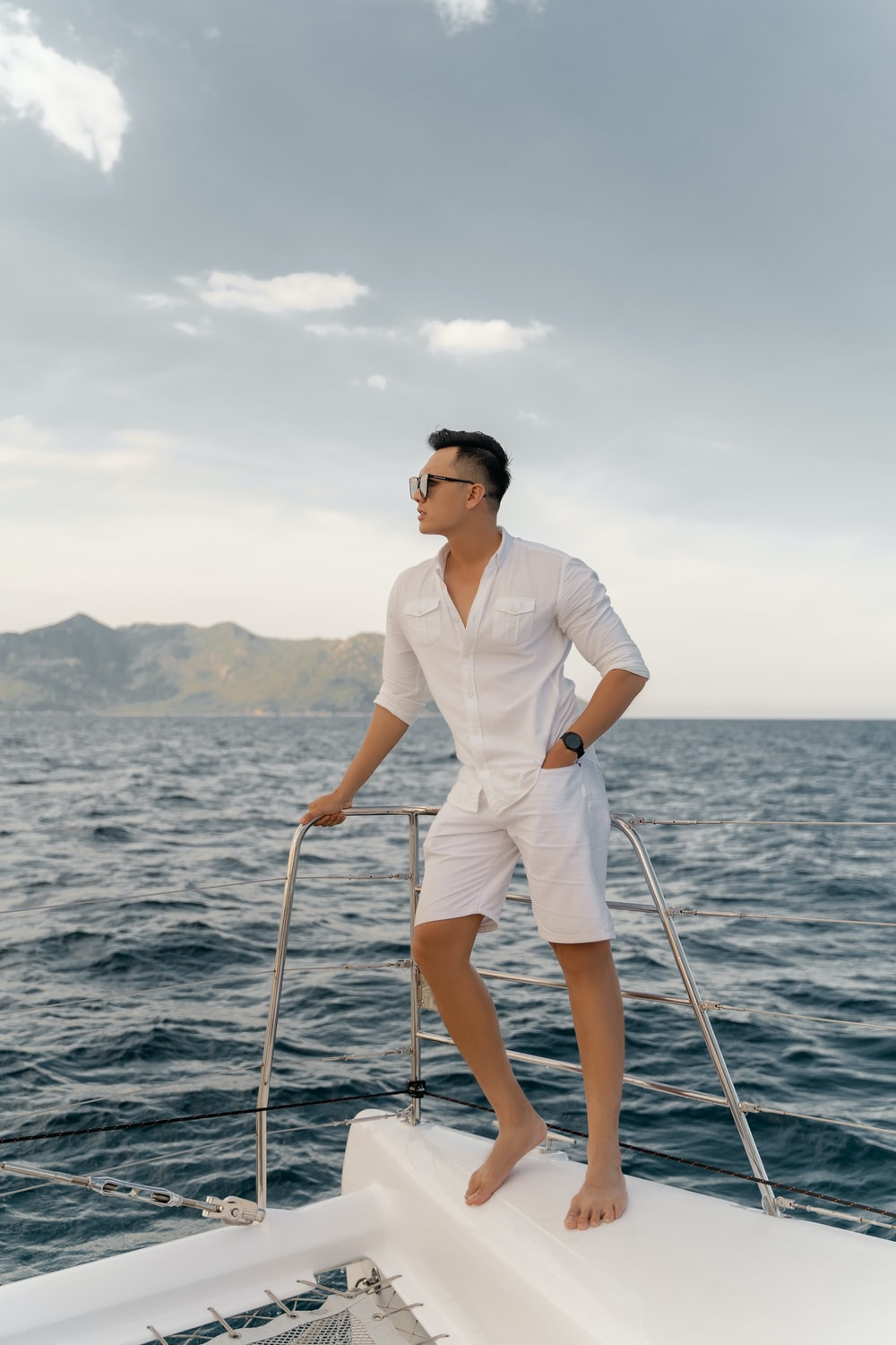 man in white polo shirt and white shorts wearing black sunglasses standing on boat during daytime