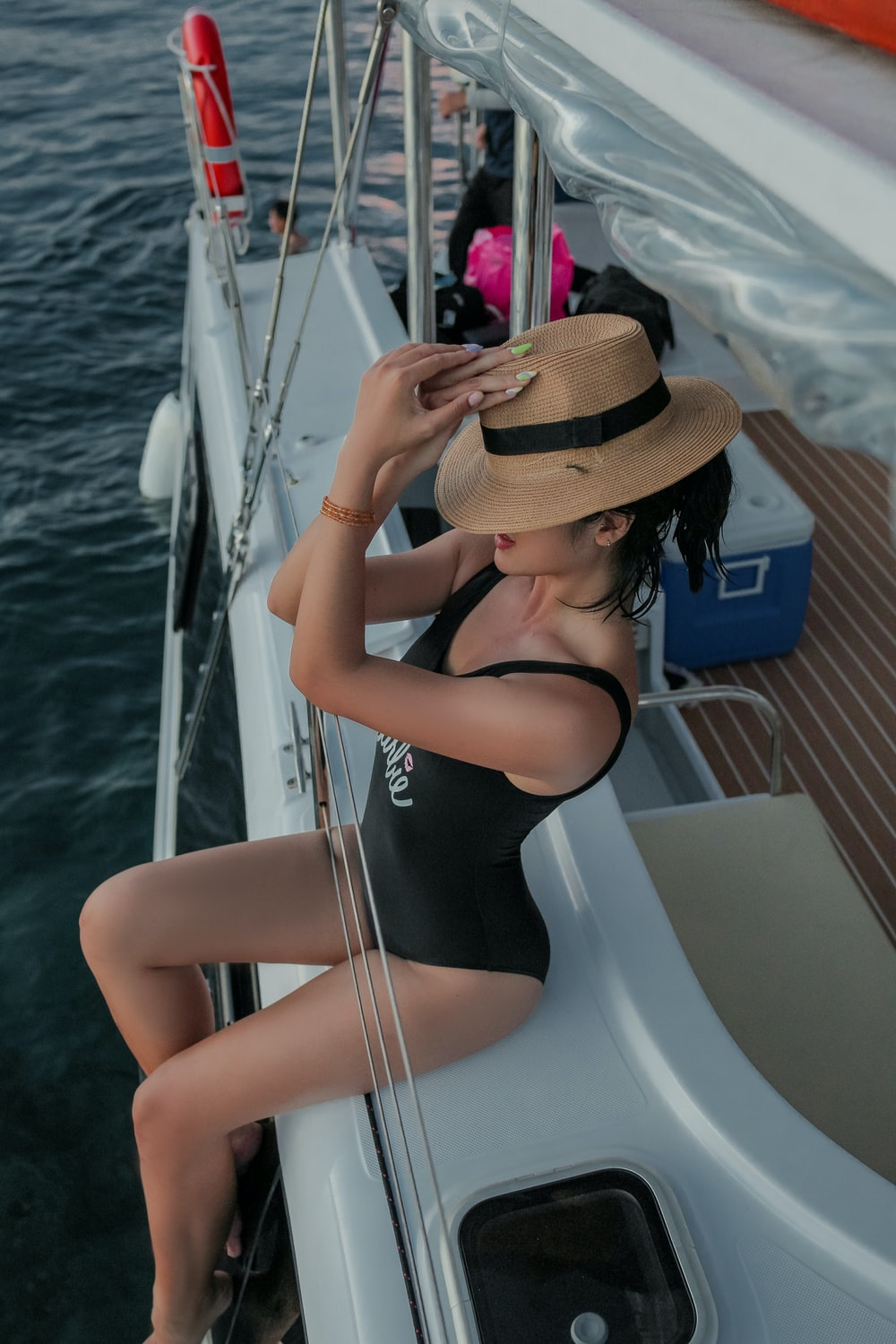 woman in black swimsuit wearing brown sun hat sitting on white boat during daytime
