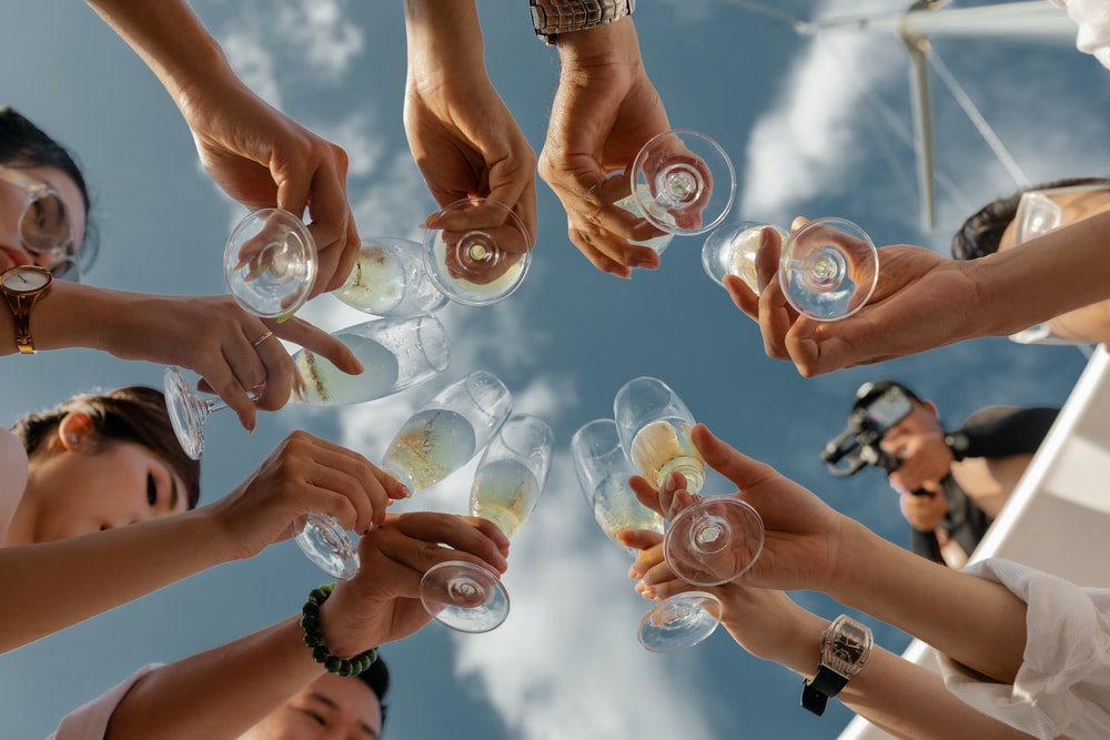 people holding clear glass bottles during daytime