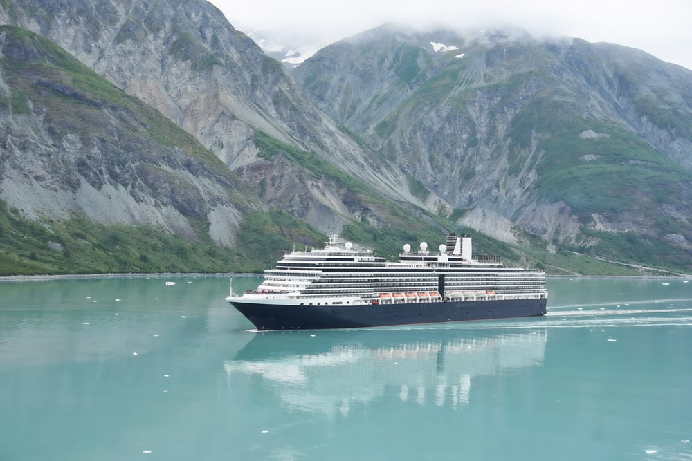 white and black cruise ship on body of water near mountain during daytime