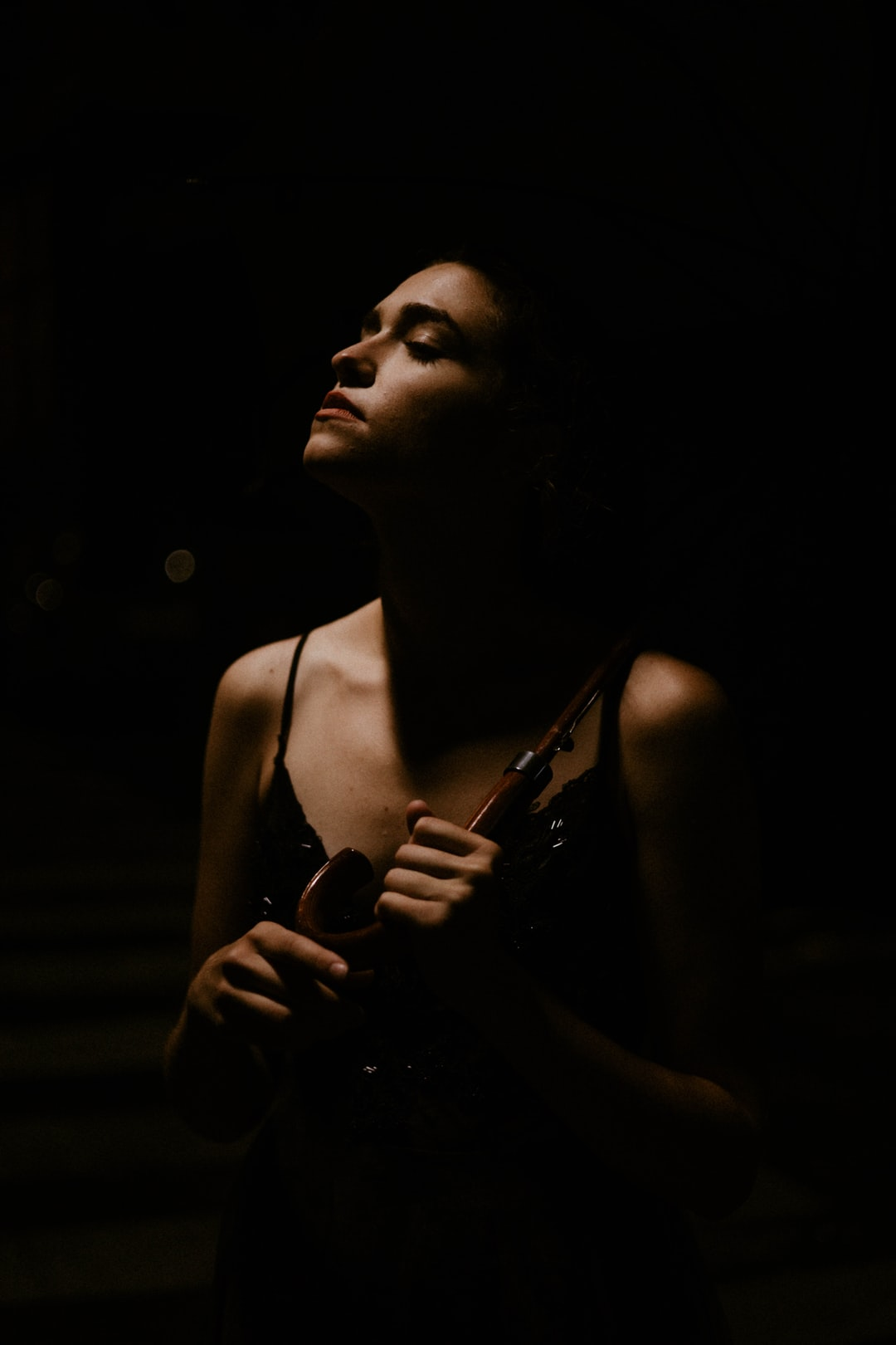 woman in white tank top holding black dslr camera