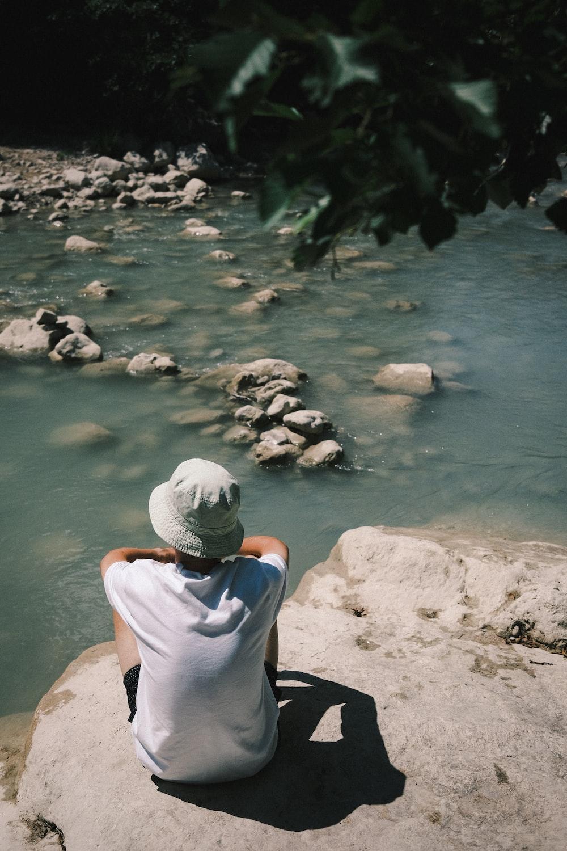 man in white shirt sitting on rock near river during daytime