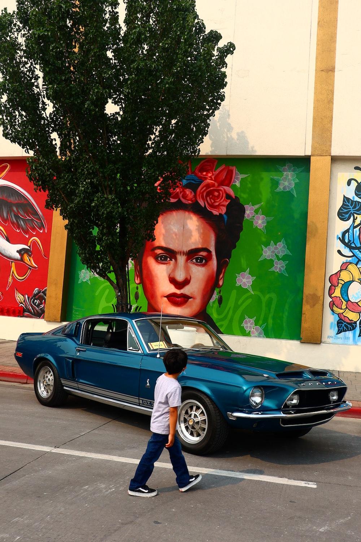 man in blue crew neck shirt standing beside black car