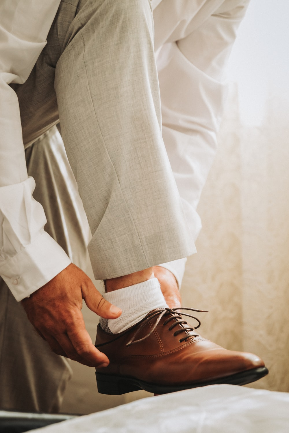 person in gray formal suit jacket wearing brown leather shoes
