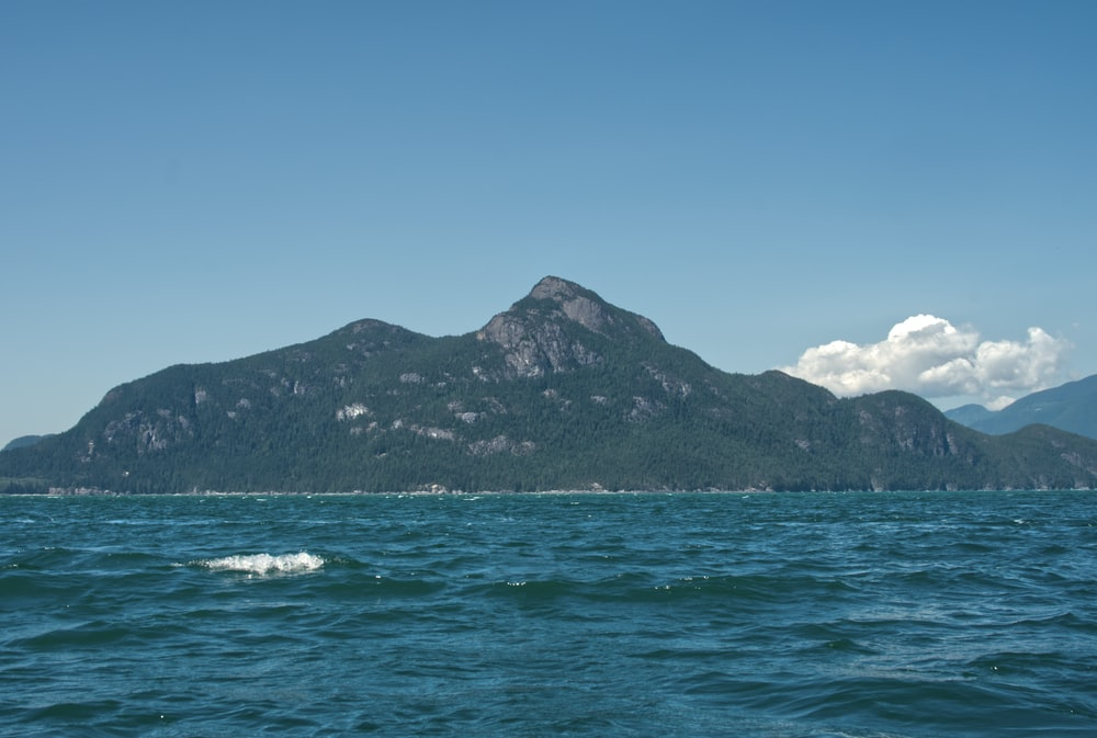 green and black mountain beside sea under blue sky during daytime