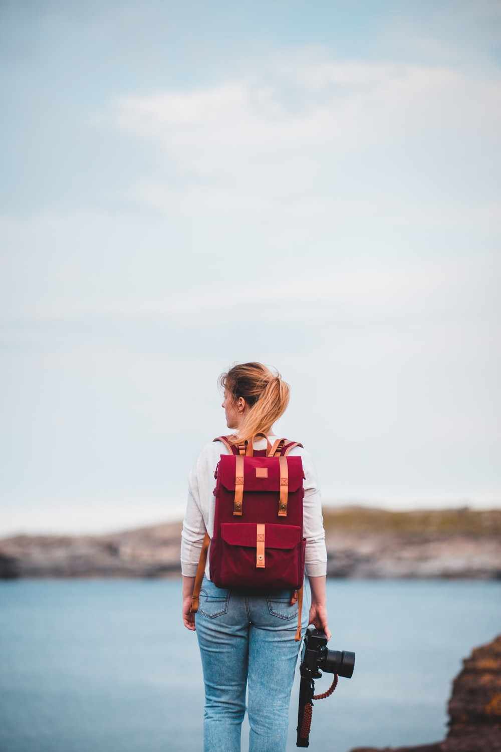 woman in white shirt and orange backpack standing near body of water during daytime