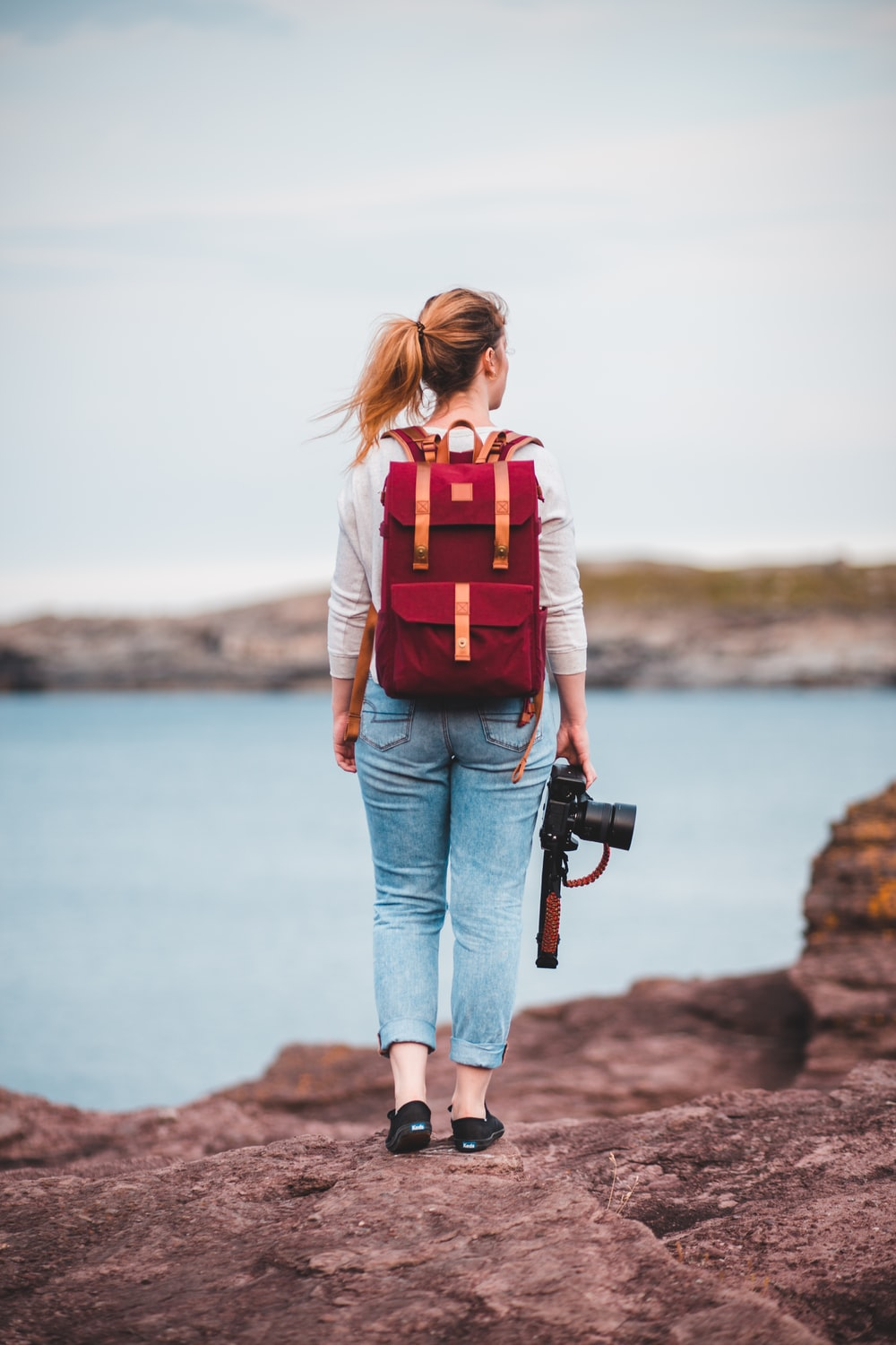 woman in blue denim jeans carrying red and black backpack standing on rock near body of near near near near