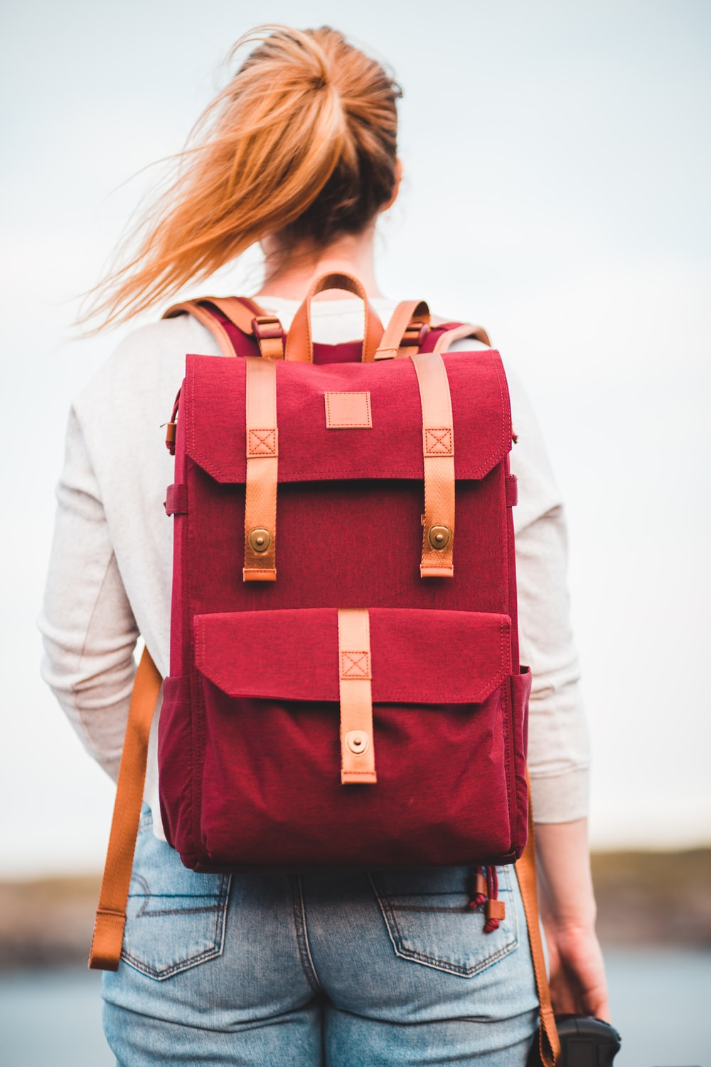 woman in white long sleeve shirt with red and black backpack