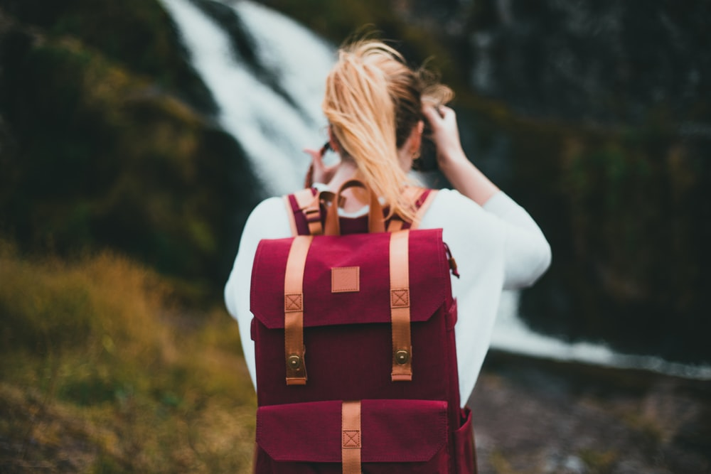 woman in white long sleeve shirt with red and brown backpack