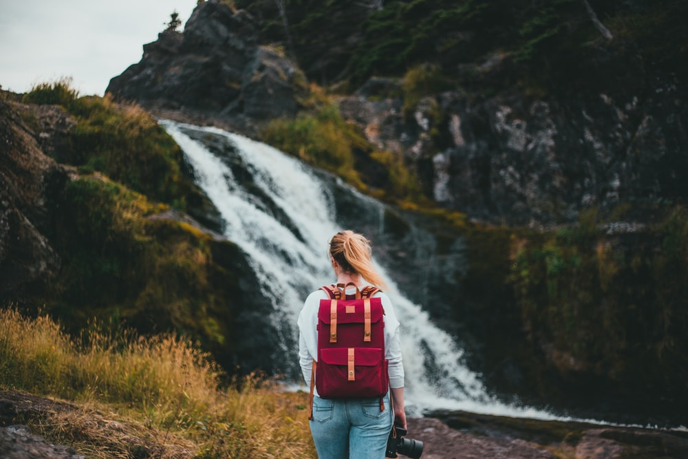 woman in red backpack standing on rocky road looking at waterfalls during daytime