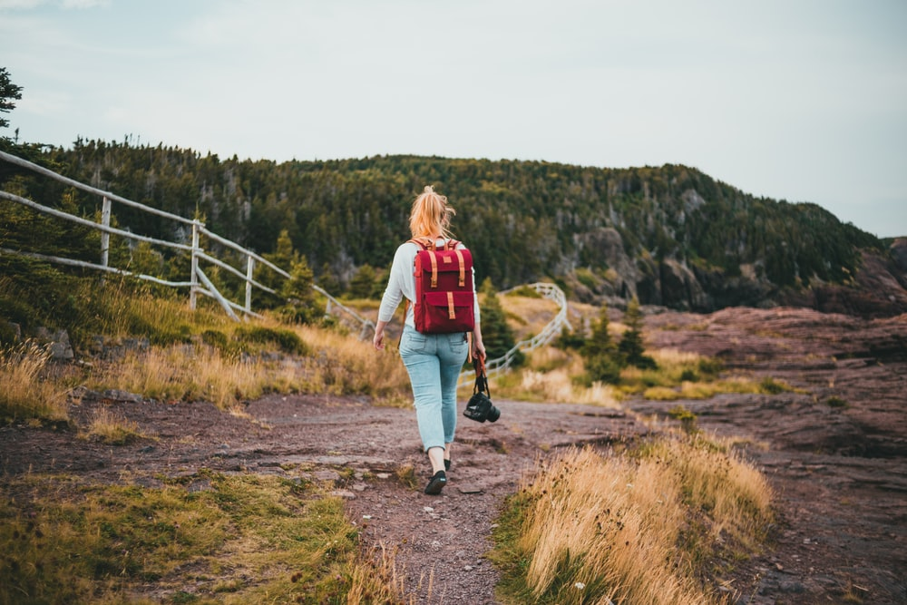 woman in red and white jacket walking on brown dirt road during daytime