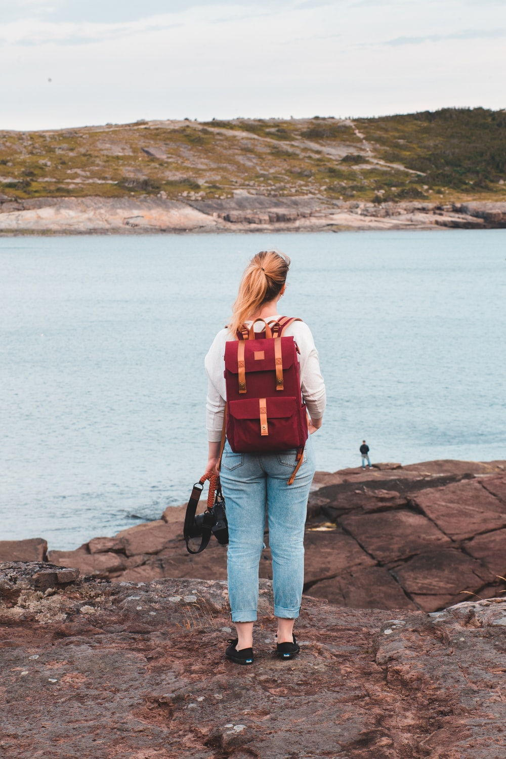 woman in red backpack standing on rock near body of water during daytime