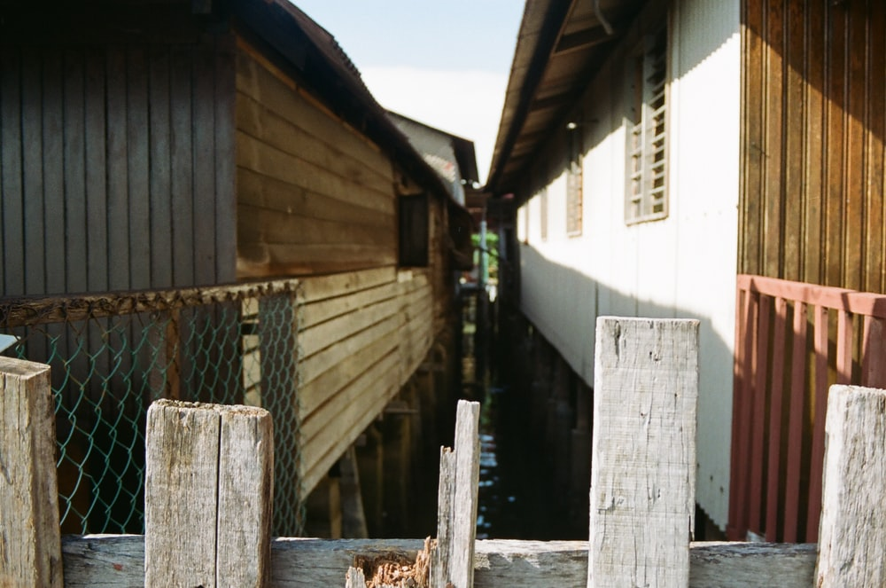 brown wooden fence on white concrete building during daytime