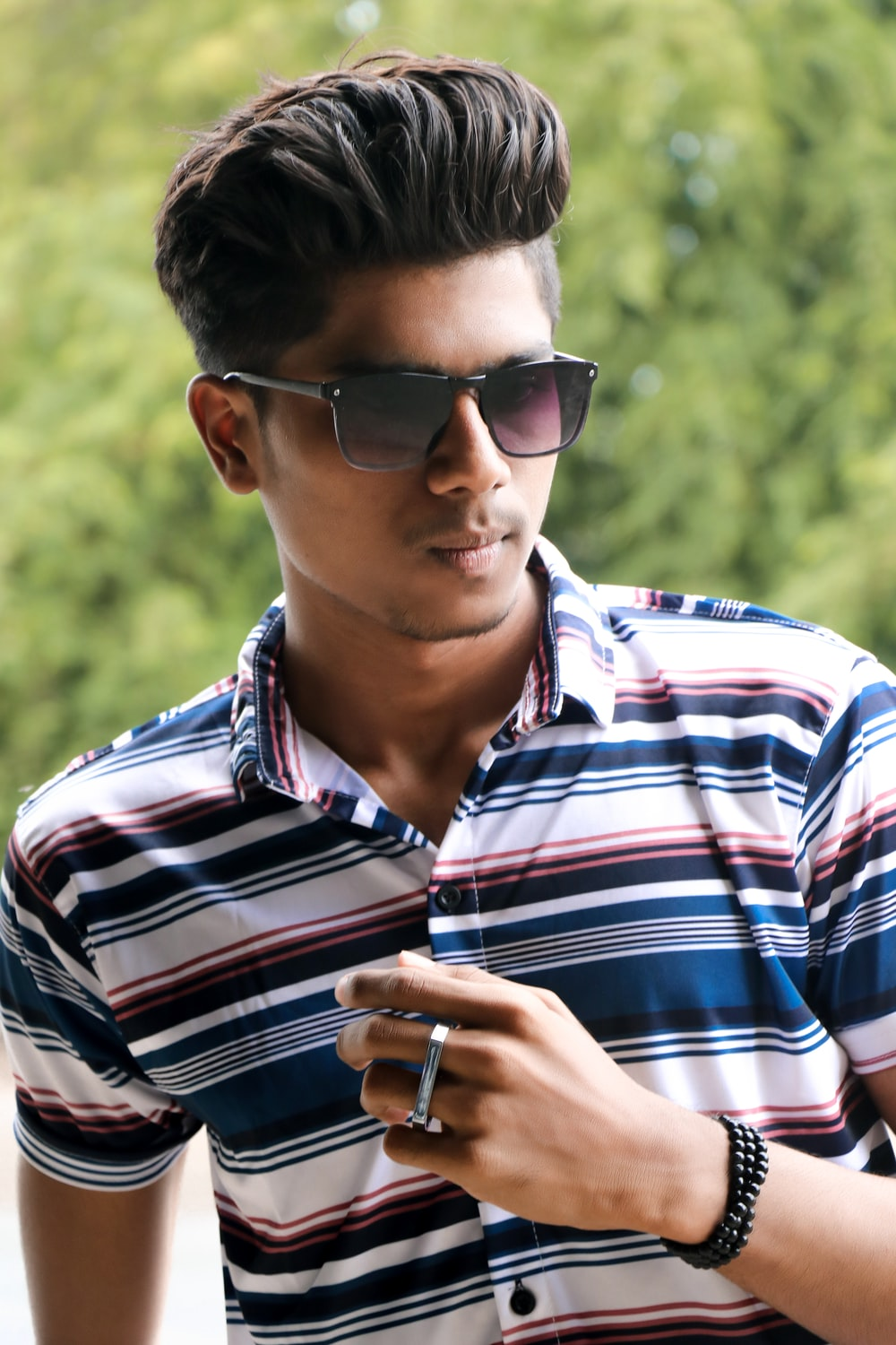 man in black white and red striped polo shirt wearing black sunglasses