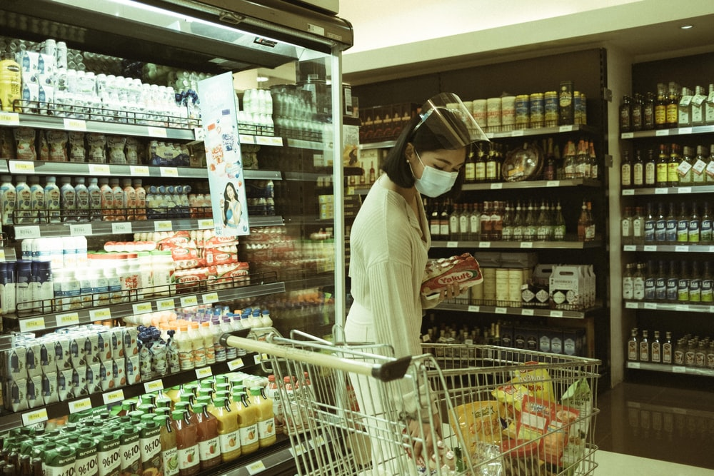 woman in white long sleeve shirt and white hijab standing in front of grocery shelf