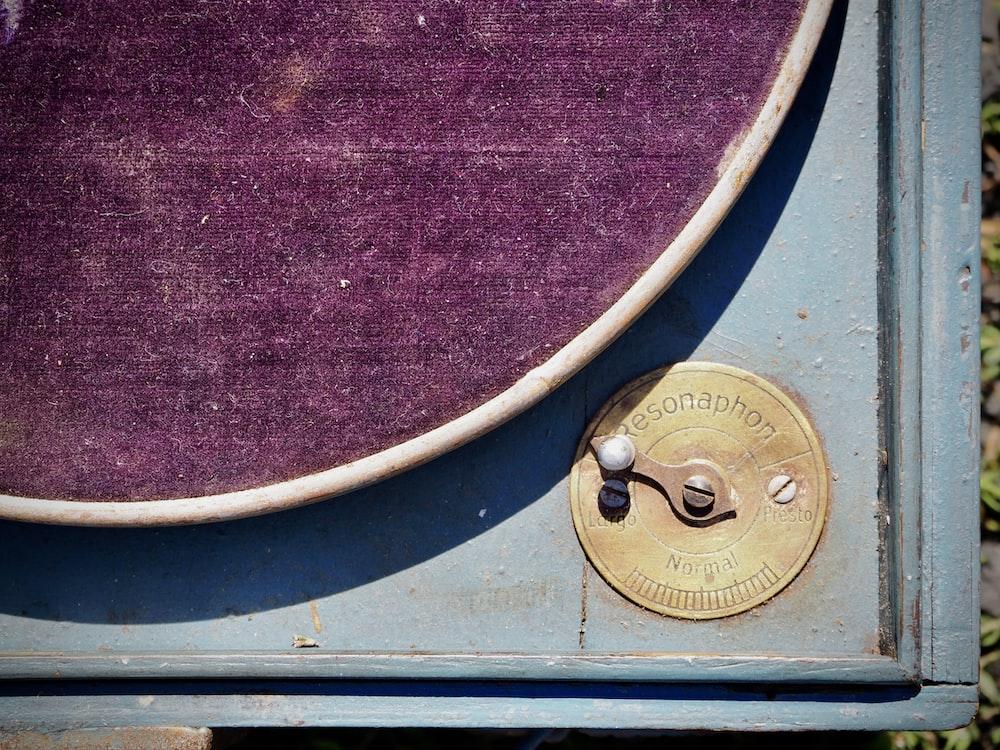 brass round door knob on purple textile