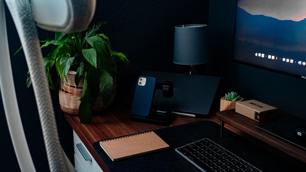 silver macbook pro on brown wooden desk