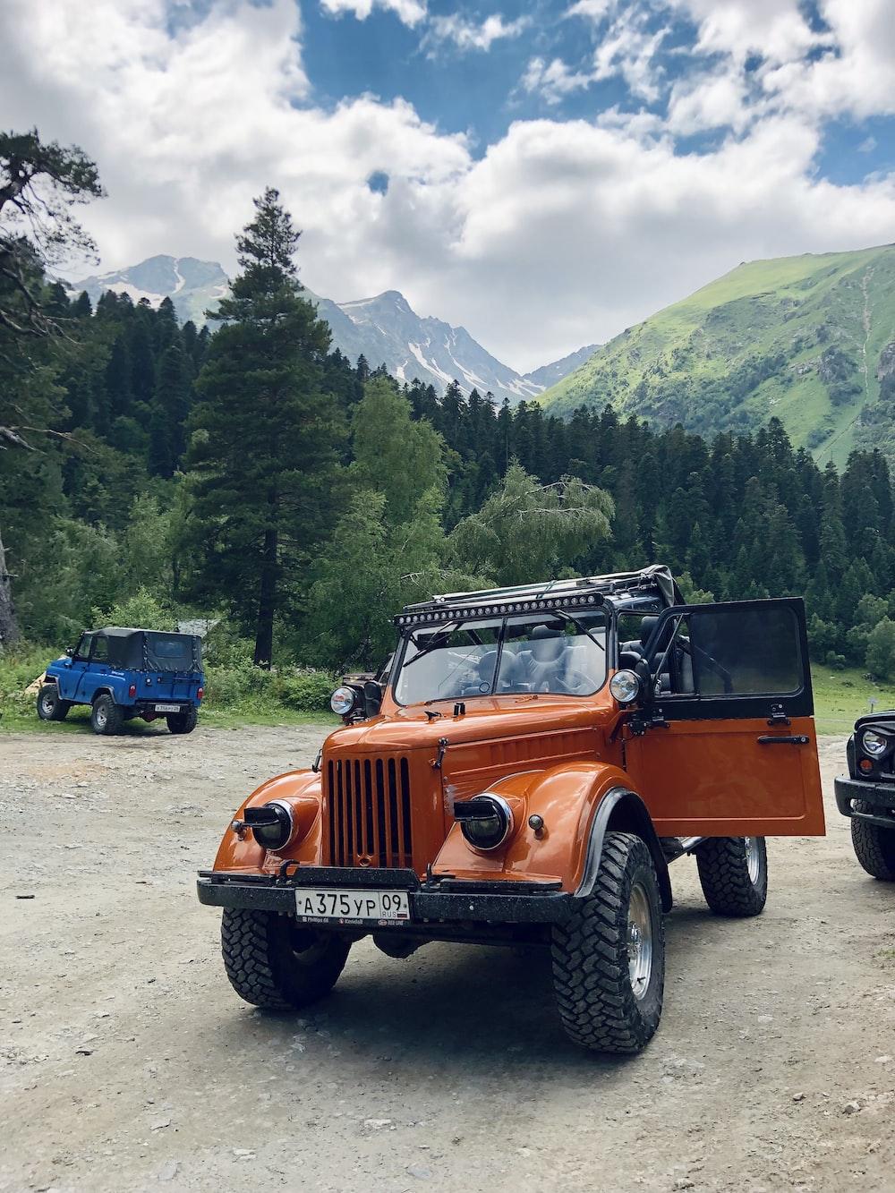 orange jeep wrangler on dirt road near green trees during daytime