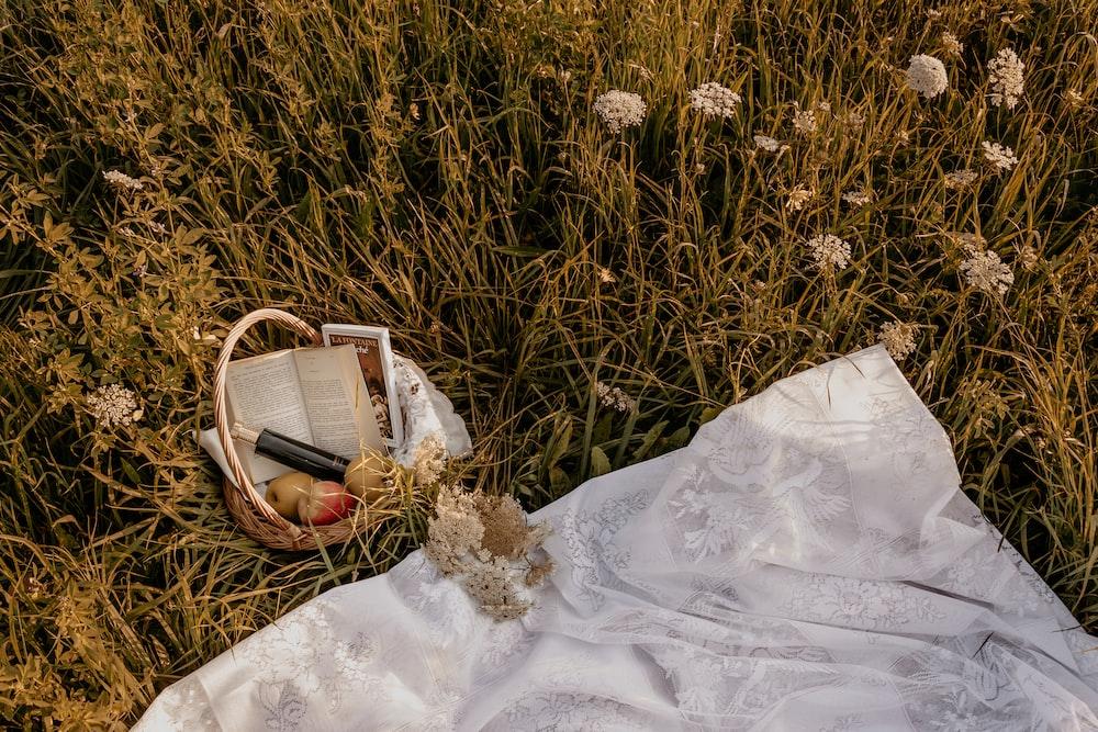 brown woven basket on white textile