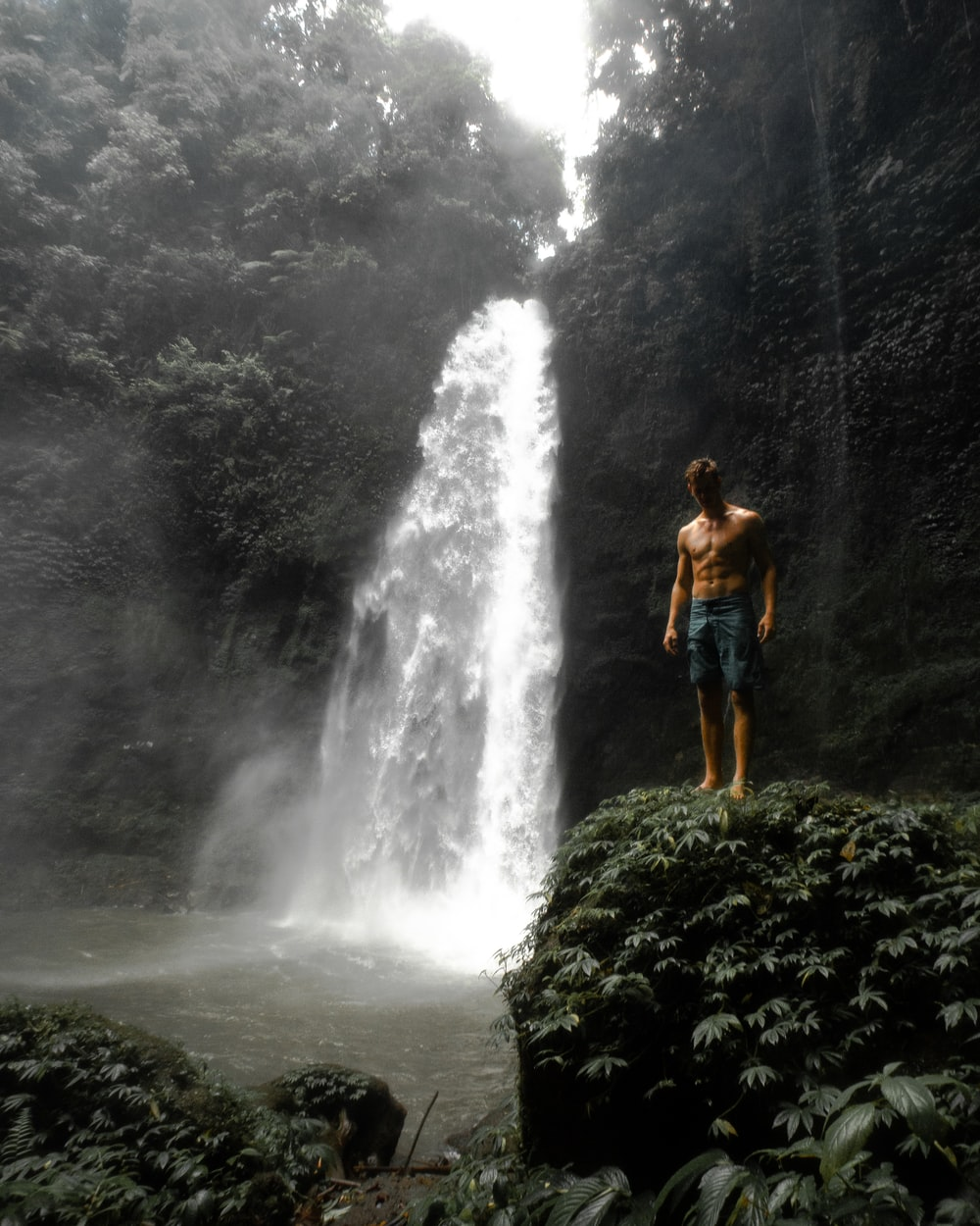 woman in blue shorts standing on rock near waterfalls during daytime