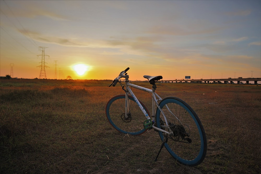 black and white road bike on green grass field during sunset