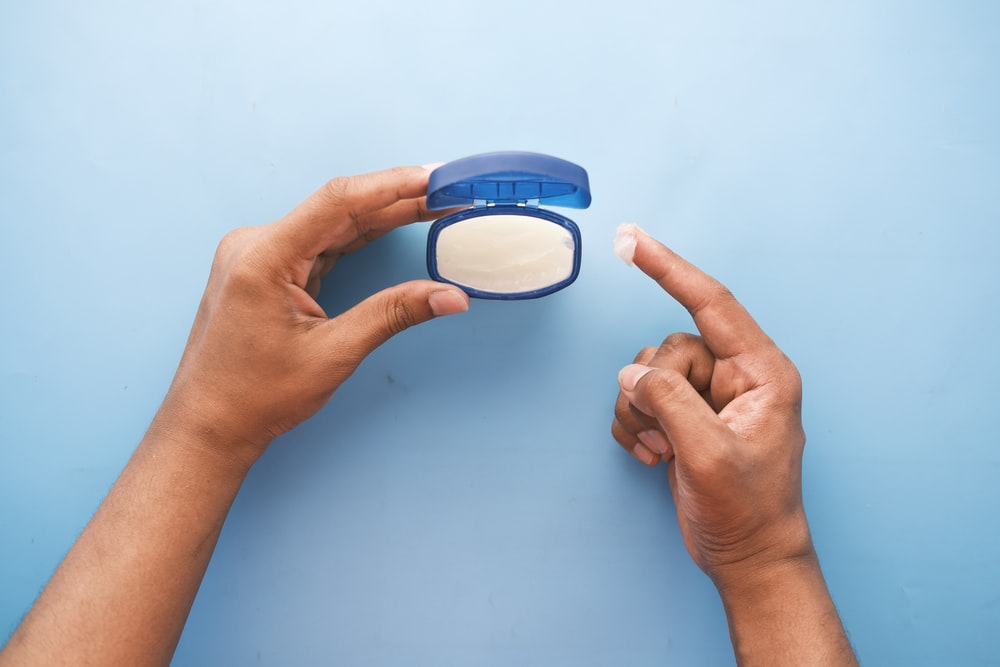 person holding blue round container