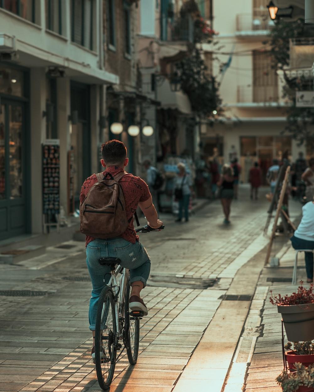 man in red jacket riding bicycle on street during daytime