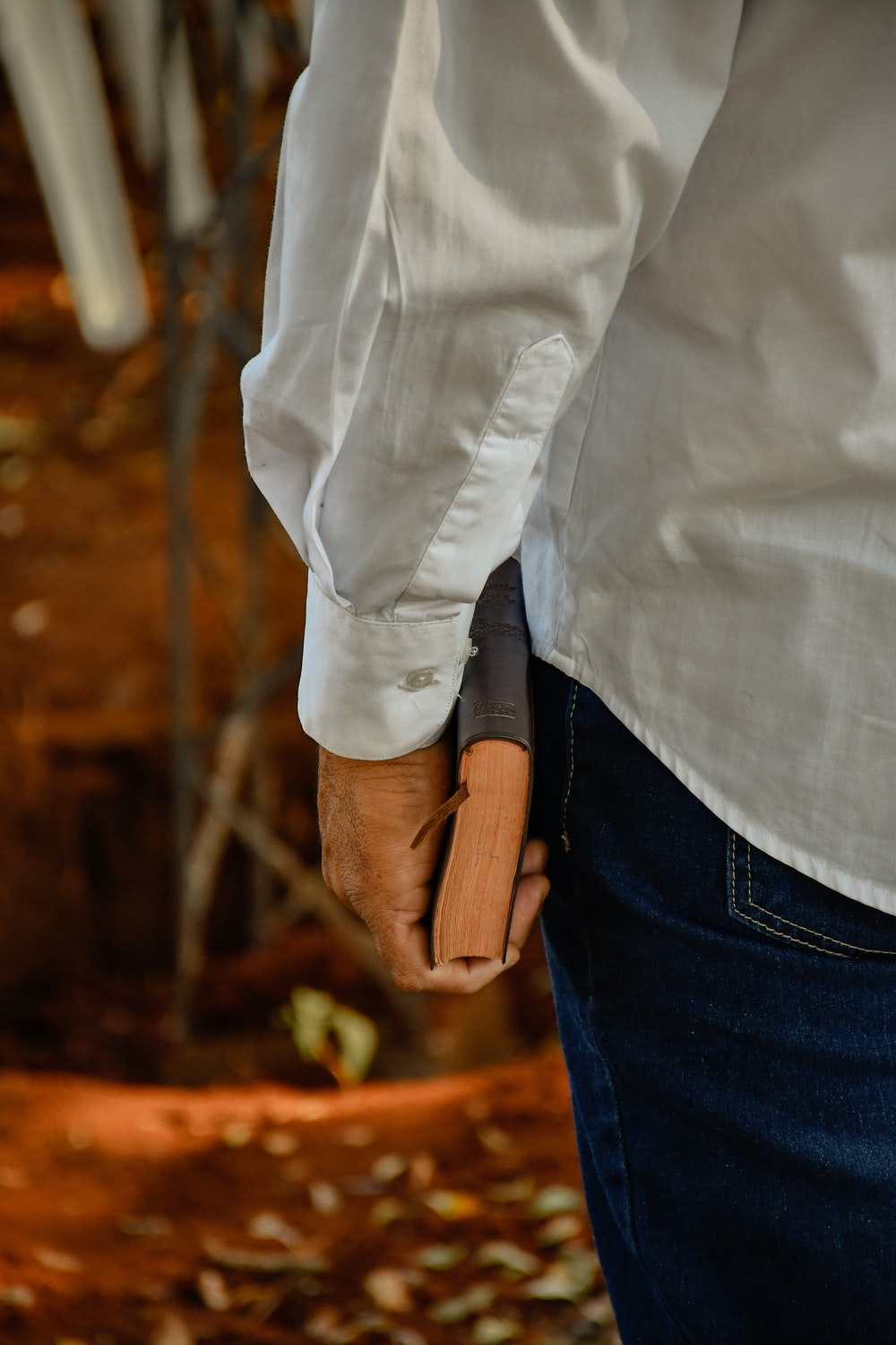 person in white dress shirt and blue denim jeans