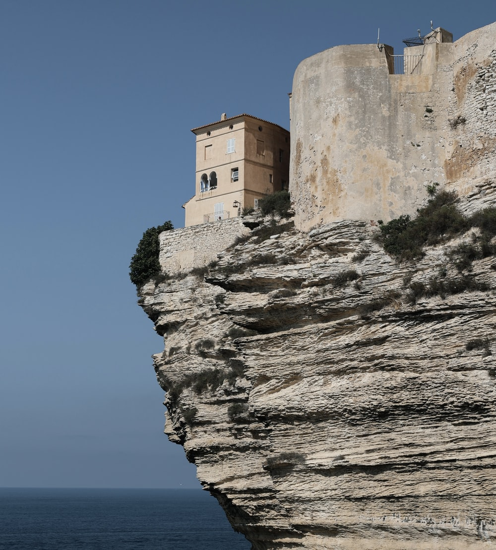 brown concrete building on cliff by the sea during daytime