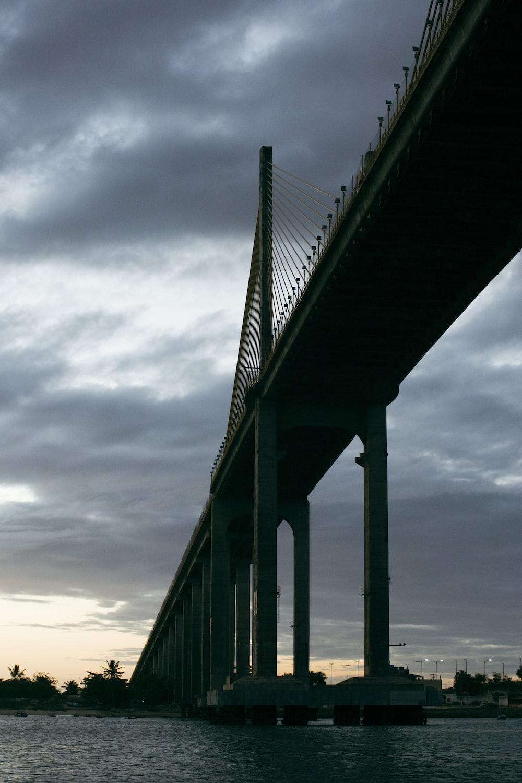 gray concrete bridge under gray clouds during daytime
