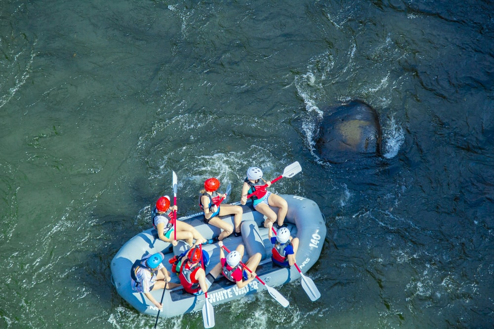 people in blue and red life vest riding on inflatable raft on water during daytime