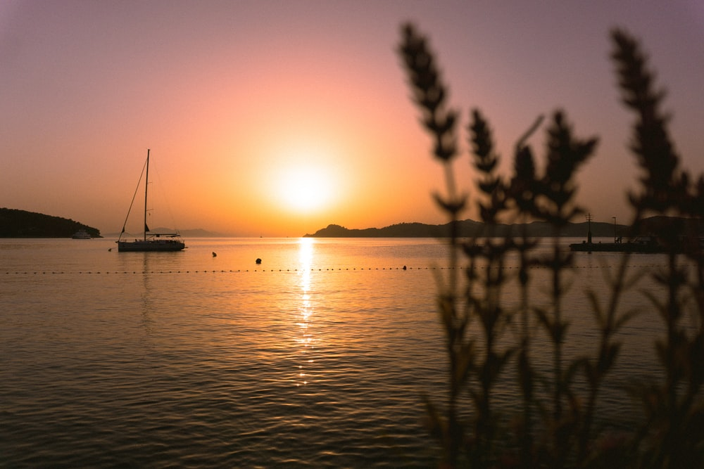 silhouette of boat on sea during sunset