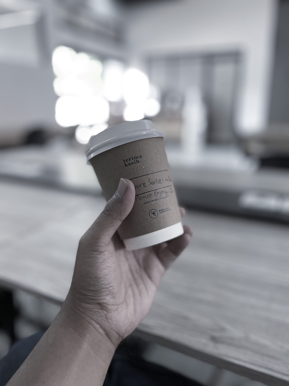 person holding brown and white disposable cup