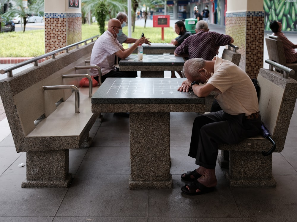 man in white t-shirt sitting on bench