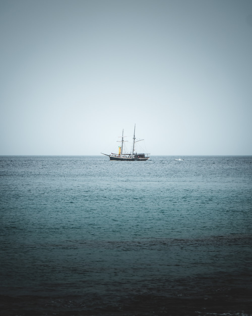 white and black boat on sea under white sky during daytime