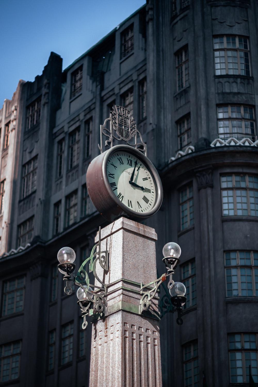 white and brown analog clock at 11 00