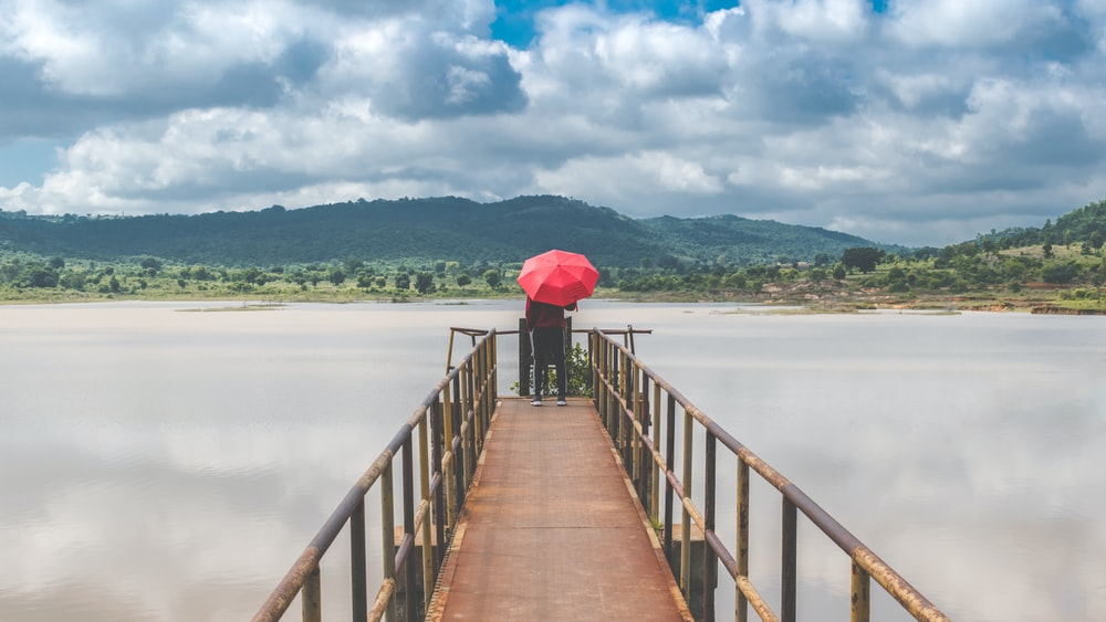 person holding red umbrella walking on wooden bridge