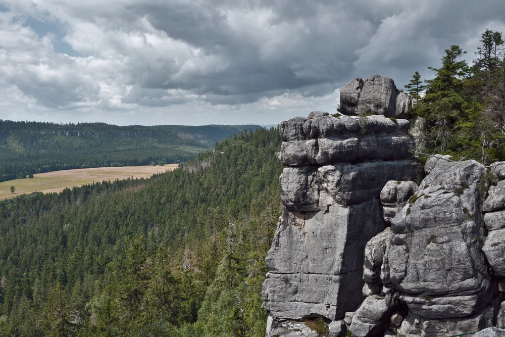 gray rock formation near green trees under white clouds during daytime